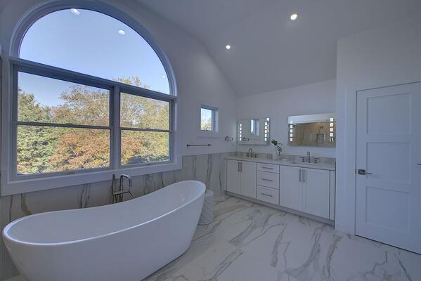 Large window over soaking tub in a white marble bathroom